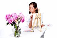 A young girl paints a picture of a vase of flowers