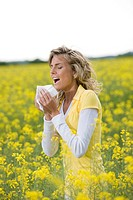 Young woman sneezing in a flowers meadow  Concept: seasonal allergy