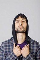 Studio shot of young man, hooded jacket