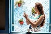 Woman text messaging by window