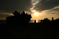 Silhouette of Marines and an amphibious assault vehicle providing security on Hwajin Beach, Republic of Korea.