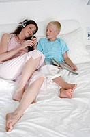 Mid adult woman with her son lying on the bed and listening to music