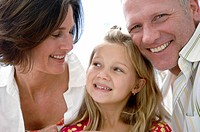 Close_up of a mid adult couple and their daughter smiling