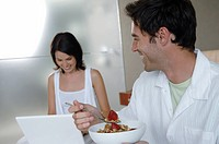 Mid adult man holding a bowl of strawberry with his wife using a laptop beside him