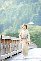 Mature woman in Kimono walking on bridge, Kyoto city, Kyoto prefecture, Japan