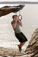 A man uses suspension rings on a beach.