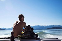 A athletic man sits and looks out after wakeboarding with snow on the mountains behind him in Idaho.