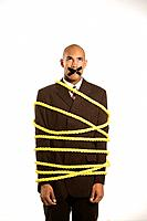 African American businessman wrapped in yellow rope with tape over his mouth.
