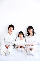 Mother, father and daughter sitting on bed