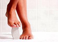 USA, Illinois, Metamora, woman standing with pumice stone under foot