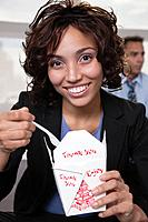 USA, New York, New York City, portrait of smiling young woman eating Chinise food
