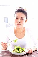 Young Woman Eating Green Salad at Table