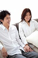 Young couple relaxing on sofa holding hands