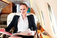Businesswoman reading newspaper on private jet