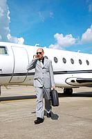 Man talking on the phone with private jet in the background