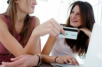 Two young women online shopping with a credit card