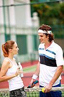 Woman talking to man at tennis court