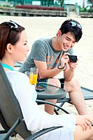 Man taking a picture of woman relaxing at lounge chair