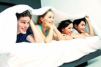 Men and women lying on bed covered by comforter