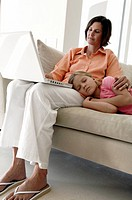 Mature woman looking at a laptop with her daughter sleeping on her lap