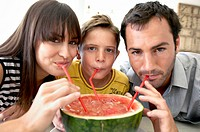 Portrait of a mid adult couple with their son drinking watermelon juice