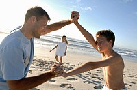 Side profile of a boy playing with his father and his sister standing on the beach