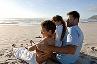 Side profile of a mid adult man sitting with his children on the beach