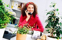 Young office employee working among pot plants