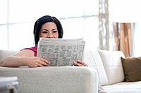 Woman sitting on sofa reading newspaper