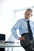 Businessman leaning on desk in office