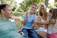 Mid adult couple with their two children enjoying in a park