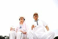 Senior couple holding bottles of water, smiling and sitting