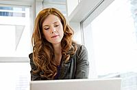 Portrait of woman in office working on laptop