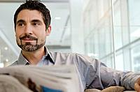 Businessman sitting in office with newspaper