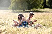 Girls using cell phones in field