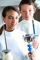 Smiling girl holding fencing trophy