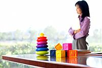 Colorful toys on table, defocused woman in background