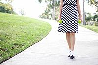 Woman walking on footpath with dumbbells, low section