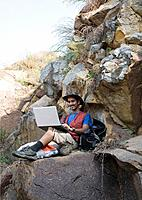 Hiker sitting on rocks and using a laptop