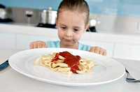 Close_up of a girl sitting at the kitchen counter in front of a plate of fettuccine