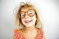 Studio portrait of smiling girl 7_9with messy hair wearing big glasses