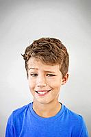 Portrait of smiling boy 13_15 with raised eyebrow, studio shot