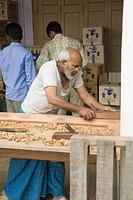 Carpenter planing a wooden plank, Chandni Chowk, Delhi, India