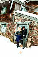 Family outside rustic house in snow