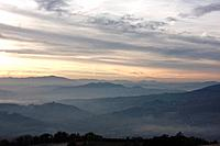 Sunrise over Tiber valley with grey pink and golden sky in the early morning mist of winter, with tree outline in foreground,and hilltop town of Todi ...