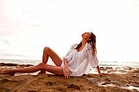 Young woman wearing white top sitting on sand, portrait (thumbnail)
