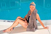 Mature woman sitting by swimming pool (thumbnail)