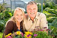 Mature couple with flowers in garden centre