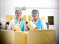 Workers holding cheese in factory