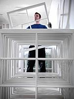 Worker holding window frames in joinery